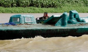 A Navy sailor drives a seized submarine, used by drug-traffickers to smuggle drugs, while displaying it to the media in Atrato River, coast of Turbo, Colombia