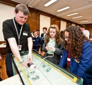 sink or swim Future Engineers Day at BAE Systems Maritime – Submarines, with Chloe McKenna of Walney School and Paris Corkill of St Bernard's Catholic High School, with Rob Chaplin, a BAE Graduate and STEM ambassador, during the testing process of the challenge