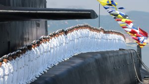 Sailors stand at attention on the nuclear submarine, stationed at the Qingdao base.