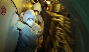 Officers walk past the submarine's nuclear reaction cabin